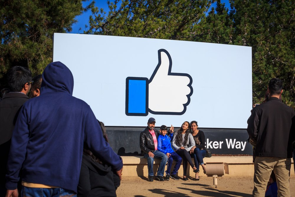 Tourists in front of a Facebook billboard