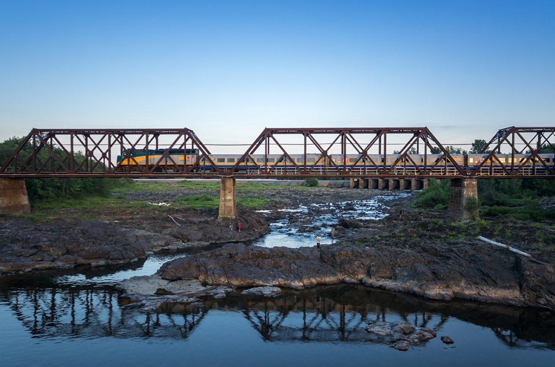 VIA Rail train driving over a bridge in Canada