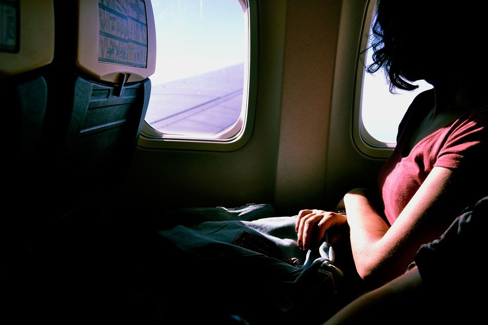 Woman looking out of a plane window