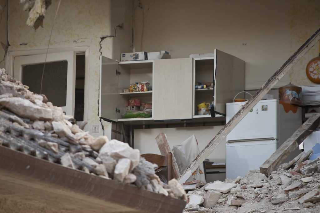 Earthquake damage to a kitchen. Rubble and fallen wall