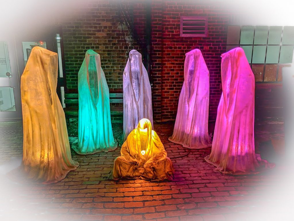 Hooded figures cloaked in light