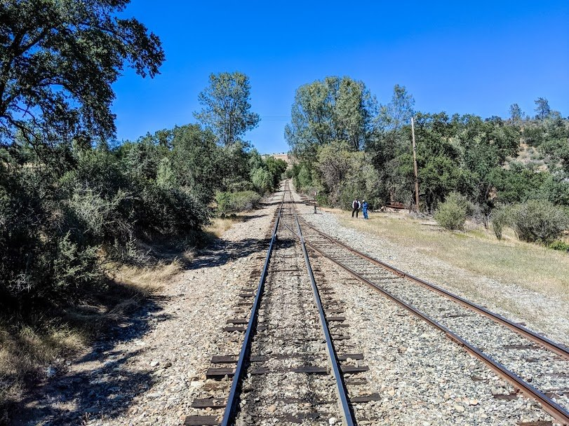 Empty train tracks with two men standing to the side