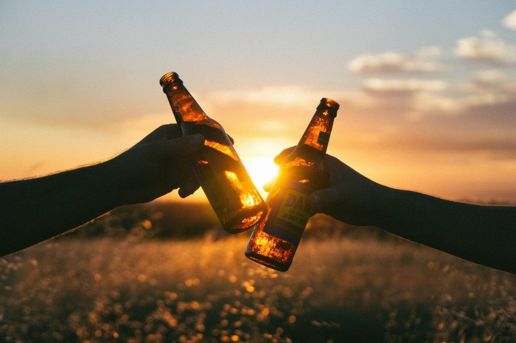 Two hands holding beer bottles in front of the sunsent