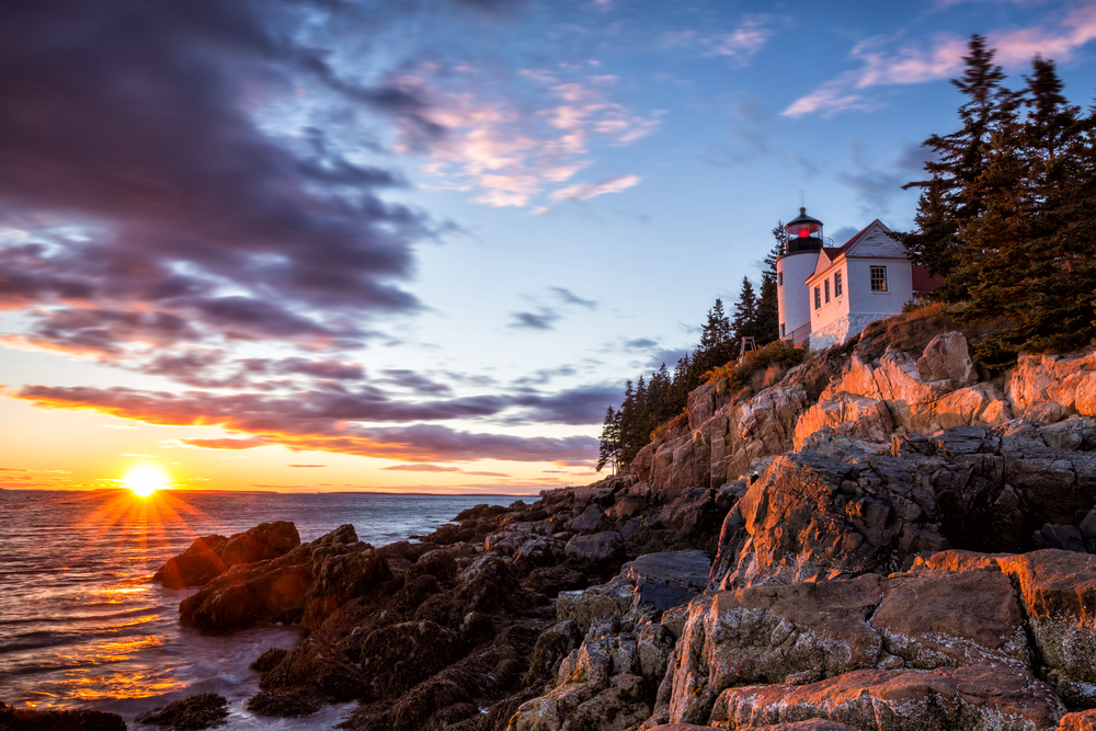 Lighthouse on a rocky coastline as the sun sets in the background